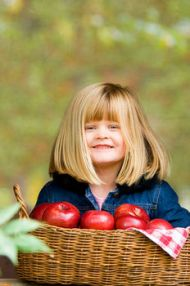 Cute Girl with a Basket of Apples